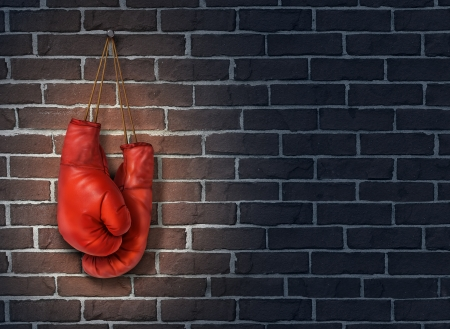 Stop competing and putting an end to business competition by hanging up a pair of red boxing gloves on a dark rustic old brick wall as a concept of stopping the fight to find the cure  Foto de archivo