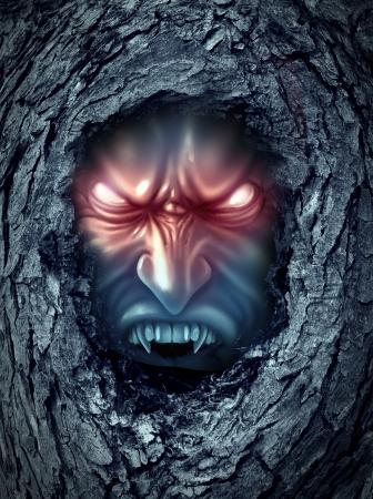 demonio: Fantasma zombie vampiro con los ojos malvados brillantes que viven dentro de un viejo tronco de árbol frecuentado oscuro como un símbolo de halloween de los malos espíritus de terror recorre el mundo de los vivos como a un demonio monstruo buscando sangre