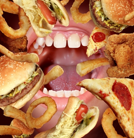 Unhealthy Eating and struggling to follow a healthy diet health concept by the temptations of fried fast food as a hamburger hot dog french fries onion rings pizza with an opened hungry mouth  Фото со стока