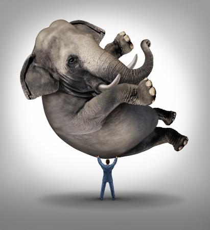 Leiderschap oplossingen zakelijk concept met een take charge zakenman het optillen van een reusachtige olifant als symbool van een sterke leider met moed en vastberadenheid om de macht los te binnen en bereiken wat onmogelijk is Stockfoto