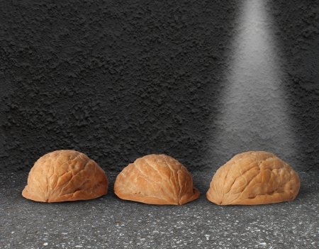 Walnut: Shell game with three walnut shells on city street pavement with a light shinning on the winning choice as a business concept of choosing the right investment with the assistance of professional guidance