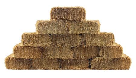 Baal hooi groep in een piramide muur patroon geïsoleerd op een witte achtergrond als een land wonen design element en landbouw boerderij en de landbouw symbool van de oogst tijd met gedroogd gras stro als gebundelde vastgebonden hooibergen Stockfoto
