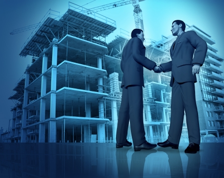 developers: Construction agreement with two business people shaking hands at a commercial realestate construction site as a concept of investing in new development for financial success  Stock Photo