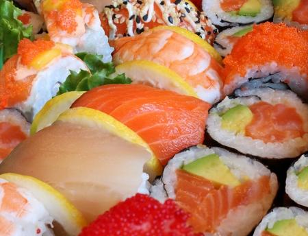 comida: Sushi japonês fechar-se com uma variedade de deliciosos pratos de peixe cru fresco preparado e frutos do mar como camarão e caviar de salmão com arroz e legumes como comida e bebida conceito de culinária asiática e catering para um estilo de vida saudável