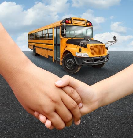 教育と学習の概念として黄色の輸送車に行く準備をして手を繋いでいる小学校の年齢の 2 つの若い学生たちと一緒に学校の子供たちのバス 写真素材