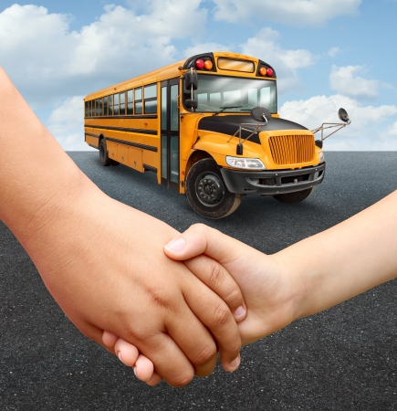 school buses: School children bus with two young students of elementary age holding hands preparing to go into the yellow transport vehicle as an education and learning concept