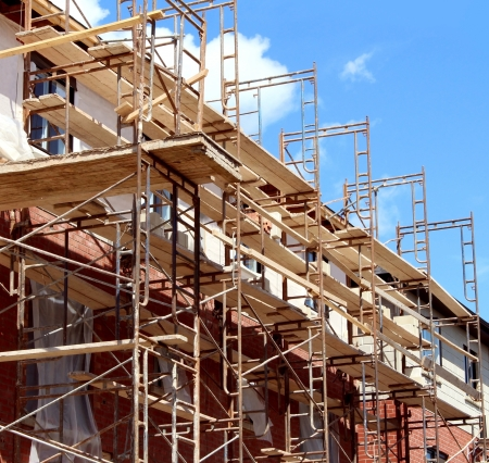property development: Residential construction in the process of being built as a real estate structure with metal scaffolding as a business symbol of economic investment rise with financial growth in a healthy economy