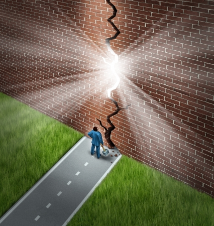Breaking the wall business concept with a businessman using a sledge hammer to break through a huge brick obstacle creating a glowing crack showing hope and opportunity through confident leadership