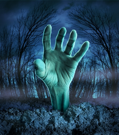 grave site: Zombie hand rising out of the ground in a spooky dark forest with creepy trees and fog as a symbol of Halloween imagination with a dangerous monster coming back from the dead