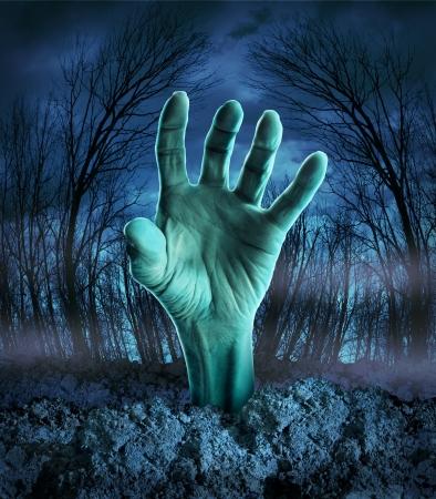 Zombie Hand steigt aus dem Boden in einer gespenstisch dunklen Wald mit gruseligen Bäumen und Nebel als Symbol für Halloween Phantasie mit einem gefährlichen Monster kommen zurück von den Toten Standard-Bild - 20688471