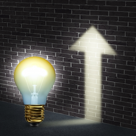 Creative direction business concept with an illuminated light bulb an upward arrow shaped glow on a brick wall as a success symbol of innovation and creativity achievement  Stock Photo - 20948390