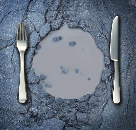 contaminacion del agua: La pobreza y el hambre concepto con un tenedor y un cuchillo en una carretera de asfalto roto en forma de un plato de comida como un problema social de las dificultades de escasez de alimentos causada por dificultades financieras o un desastre natural que resulta en que viven los pobres en las calles como un riesgo para la salud