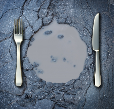 famine: Poverty and hunger concept with a fork and knife on a broken asphalt road shaped as a dinner plate as a social problem of food shortage hardships caused by financial distress or natural disaster resulting in living poor on the streets as a health risk