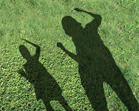 unkind: Bullying kids and school bully concept with the shadows of two children with one smaller child being threatened and abused by the older kid on green grass as a symbol of school safety from bullies  Stock Photo