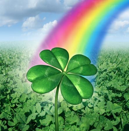 Geluk concept met een klavertje vier op een gebied van groene klavers met een regenboog van de hemel te stralen naar beneden als een symbool van geluk en voorspoed als een metafoor voor succes en kansen Stockfoto