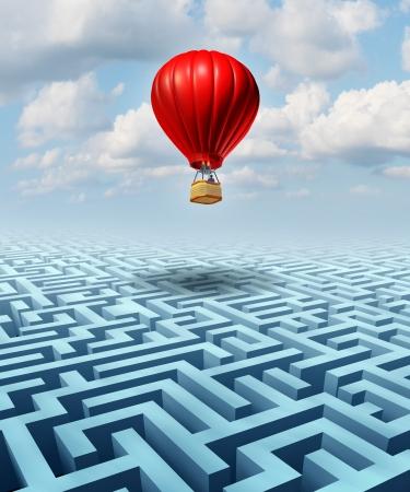Superare le sfide di business e concetto di vita con una mongolfiera rossa con un uomo d'affari all'interno di volare sopra un labirinto di confusione o di puzzle del labirinto come metafora per conquistare il successo avversità con la leadership