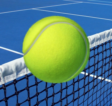 tennis serve: Tennis sport concept with a ball flying over the court net or netting as a leisure fitness and exercise symbol and health care icon for recreational exercising and living a fit lifestyle