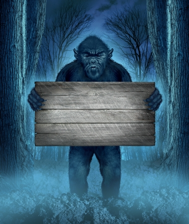Monster holding a rustic blank old wood sign as a creepy halloween concept with a werewolf lurking as a bigfoot creature coming out of a dark scary background with a moon glow behind it as a horror symbol of a haunted woods animal  photo