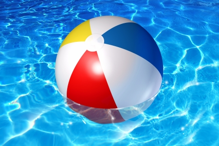 Pool fun concept with an inflatable plastic beach ball floating in cool crystal clear reflective water as a symbol of vacation relaxation in a family backyard or liesure activity at a holiday hotel