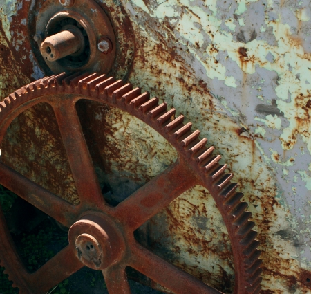 fade away: Broken industry business concept with old abandoned vintage metal gears and a cog wheel that are weather damaged and rusting away as a symbol of a prosperous manufacturing time gone by