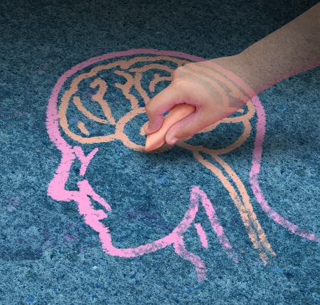 Children education concept  and school learning development with the hand of a child drawing a human head and brain with chalk on a cement floor as a symbol of mental health issues in youth