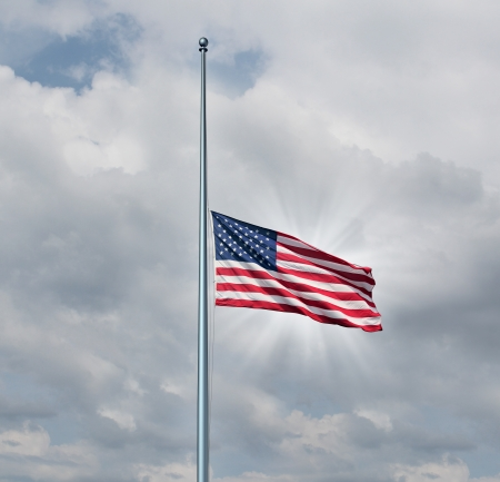 united states flags: Half mast American flag concept with the symbol of the United States flying at low level on the flagpole or staff on a cloudy day with a sun glow as an icon of honor respect and mourning for fallen heros  Stock Photo