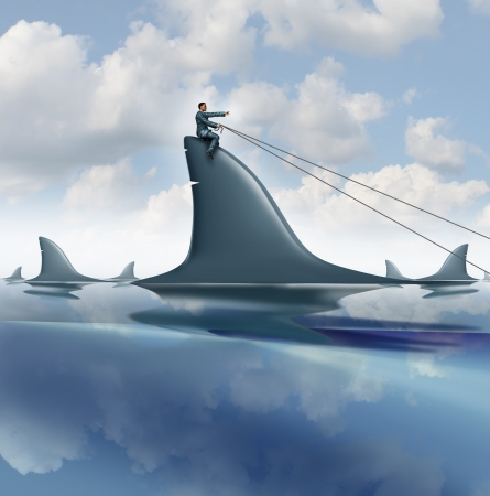 domination: Risk control business concept with a courageous businessman riding a dangerous shark in the ocean guiding it for success controlling and managing uncertainty as a symbol of leadership   Stock Photo
