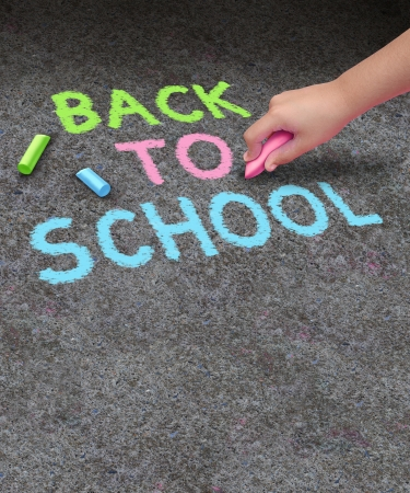 sidewalk sale: Back to school chalk drawing with blank area  for copy space on a concrete sidewalk with the hand of a child holding a color as a symbol of education and the start of the school year for learning