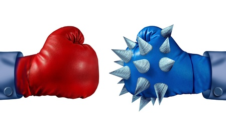 superiority: Competitive advantage and determination to win with two competing business people wearing boxing gloves but with one businessman who is more prepared to fight because he has metal spikes on his equipment  Stock Photo