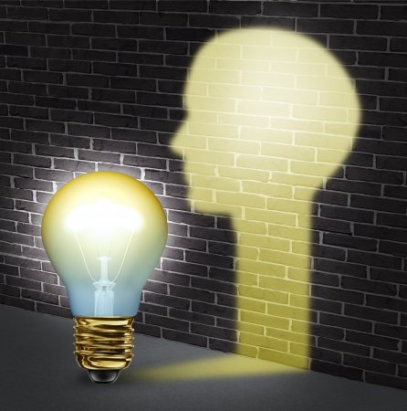 creative communication: Creative communication and freedom of expression with an illuminated light bulb shinning a glow shaped as a human head glowing on a brick wall as a business concept for innovation and new bright leadership thinking