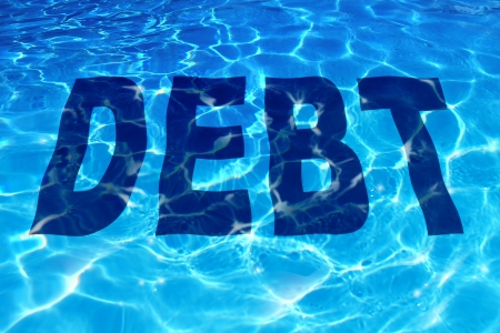 Drowning in debt business and finance concept with the word icon sinking under a sparkling reflection of blue pool of water as a symbol of financial problems to pay debts owing resulting in budget management desperation