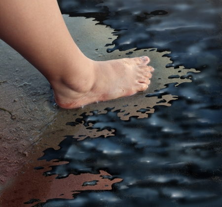 sludge: Oil spill or petroleum slick concept with the foot of a child walking on a sandy beach turned into a disaster zone with oily black sludge polluting the marine life as a man made catastrophe and environmental disaster symbol  Stock Photo