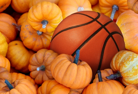 Thanksgiving Day basketball and autumn sports during harvest\ time with a holiday tournament ball in a pile of orange pumpkins as\ a concept for living a healthy lifestyle and eating natural food\ with fitness through exercise