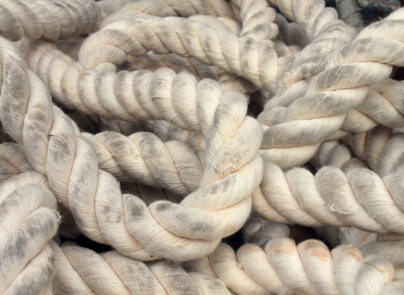Marine rope as a life line concept for a boat or yacht in a tangled and twisted position laying down on a deck as a nautical symbol of sailing preperation and confusion from the knotted white twine background  Stock Photo - 22141096