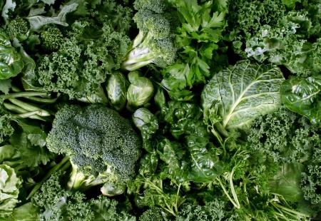 Les légumes verts et fond sombre alimentaire feuillu comme un concept de manger sain de produits frais du jardin cultivés biologiquement comme un symbole de la santé comme le chou frisé bettes épinards chou brocoli et le chou