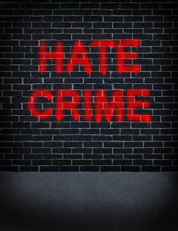 bigotry: Hate crime social problem concept with a dark grey brick wall with graffiti spray can paint painted on the building structure as a symbol of racism and race discrimination as an illegal racial act of hatred and vandalism based on fear and xenophobia