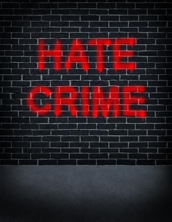 conflictos sociales: Odio concepto crimen problema social con una pared de ladrillos de color gris oscuro con graffiti aerosol puede pintar pintado en la estructura del edificio como un s�mbolo del racismo y la discriminaci�n raza como un acto ilegal de odio racial y el vandalismo basada en el miedo y la xenofobia Foto de archivo