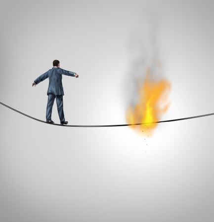 adversity: Increasing risk business concept and metaphor for overcoming adversity and dangers in following a risky strategy facing the end of the line as a businessman walking and hanging from a burning thread on a hazardous high wire