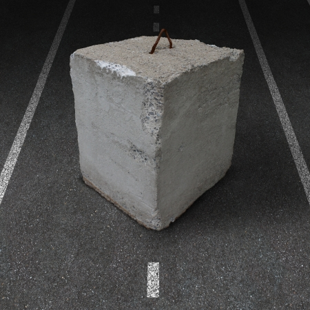 barrier: Roadblock obstacle and barrier business concept with a huge cement or concrete cube barricade blocking a road or highway as a symbol of restricted opportunity or political gridlock resulting in government or financial system shutdown  Stock Photo