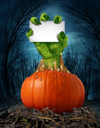 monster movie: Zombie pumpkin sign with a green hand holding a blank sign card as a creepy halloween or scary symbol with textured skin wrinkled monster fingers coming out of a wet open pumpkin in a dark spooky forest