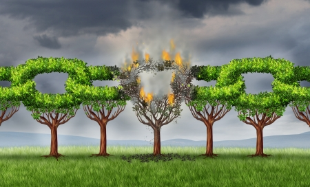 severed: Chain breaking business concept with a group of linked trees shaped as connected links that are being broken and detached with a burning  fire as a metaphor for ruptured network problems on a storm sky  Stock Photo
