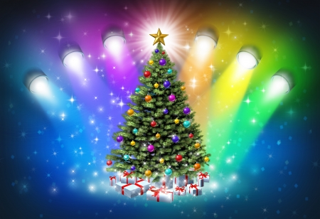 winter theater: Christmas spotlights with rainbow colors as a festive magical abstract background of winter and new year celelebration with lights shinning on a decorated pine tree with gifts and a glowing star  Stock Photo