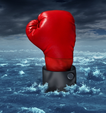 compete: Drowning the competition business concept with the hand of a businessman wearing a red boxing glove reaching up struggling to survive in turbulent ocean water as a metaphor for crisis and losing the battle to compete in the financial world  Stock Photo