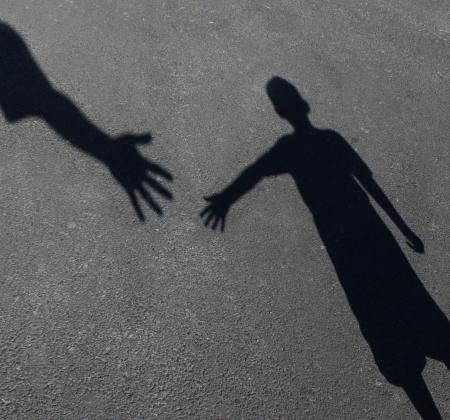 inspirerend: Helpende Hand met een schaduw op de stoep van een volwassen hand hulp aanbieden of therapie aan een kind in nood als een onderwijs concept van naastenliefde jegens behoeftige kinderen en leerkracht begeleiding aan studenten die behoefte hebben tutoring