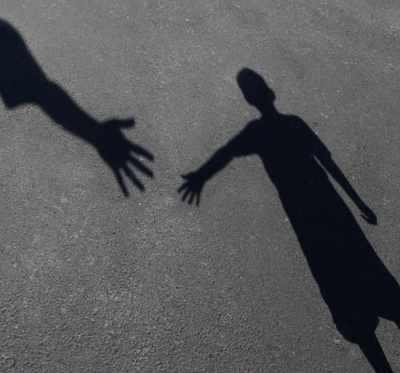 Helping Hand with a shadow on pavement of an adult hand offering help or therapy to a child in need as an education concept of charity towards needy kids and teacher guidance to students who need tutoring