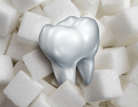 sweet tooth: Sweet tooth dental health care concept with a single molar in a pile of sugar cubes as a health and diet symbol for craving sweetened foods that are bad for your health and diabetes risk diabetes risk
