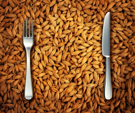 food fight: Eating wheat food as a health concept with a background of golden natural cereal grains and a place setting with a knife and fork as diet and dieting symbols of  baked goods as bread cake and pasta or an icon of feeding the poor  Stock Photo