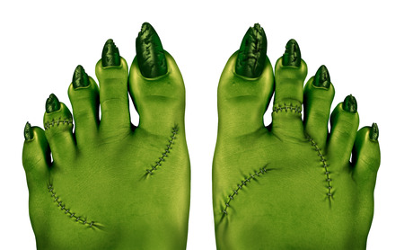 monster movie: Zombie feet as a creepy halloween or scary symbol with textured green skin wrinkled monster toes and foot stitches isolated on a white background as a spooky design element