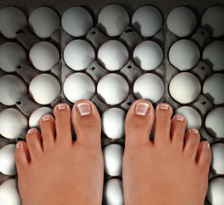 treading: Walking on eggs as an emotional concept of anxiety and stress for treading carefully on a dangerous fragile path as a metaphor for challenges risk and security with barefoot human feet stepping on white eggshells