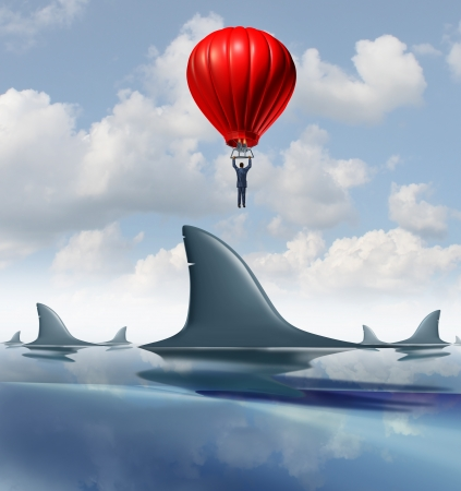 risky innovation: Avoid danger and rise above the risk as a business concept for innovative strategies and leadership solutions to difficult financial challenges as a businessman flying in a hot air balloon over dangerous group of sharks
